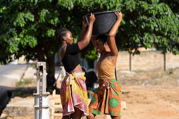 Schöne afrikanische frauen, die wasser holen