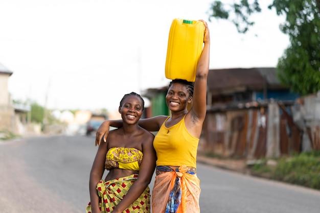 Schöne afrikanische frauen, die wasser von draußen holen