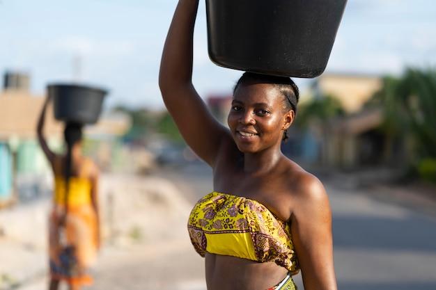 Schöne afrikanische frauen holen wasser von außen