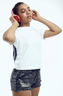 Schöne afrikanische jugendliche mit dreadlocks in hörender musik der sportkleidung