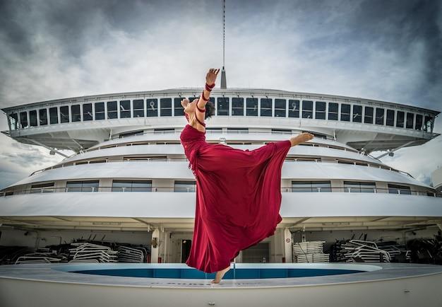 Schöne afrikanische tänzerin mit schwarzem haar, die ein rotes kleid trägt, das auf dem bug des schiffes auf der brücke im hintergrund tanzt.
