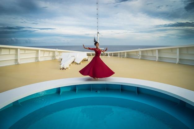 Schöne afrikanische tänzerin mit schwarzem haar, die ein rotes kleid trägt und auf dem bug des schiffes mit pool und anker tanzt.
