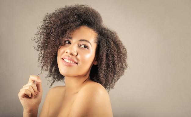 Schöne afroamerikanerfrau, die um ihrem gelockten haar sich kümmert