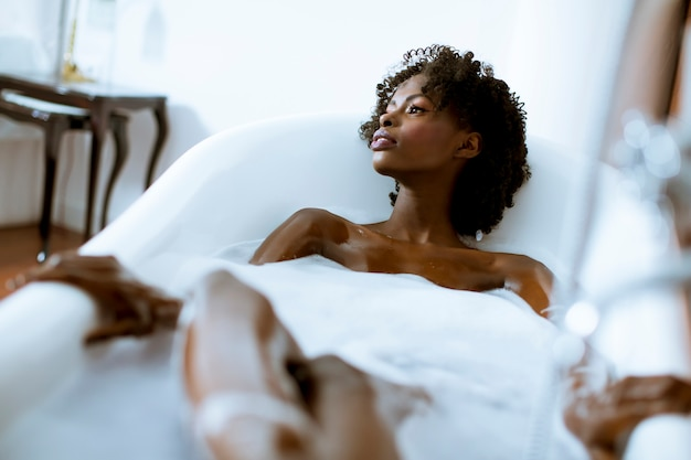 Schöne afroamerikanerfrau, die voll in einer wanne schaum badet