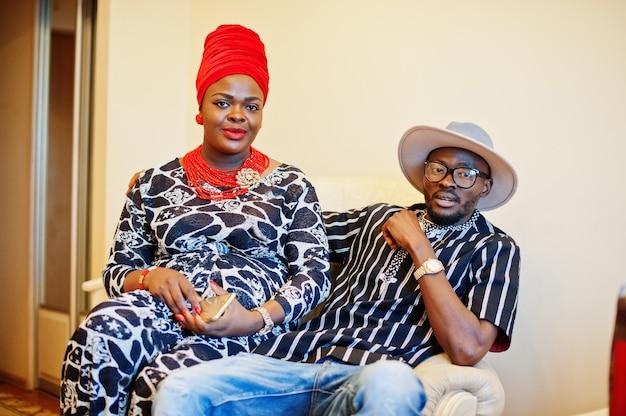 Schöne afroamerikanerfrau im trachtenkleid und im hübschen sitzen und im lächeln des schwarzen mannes.