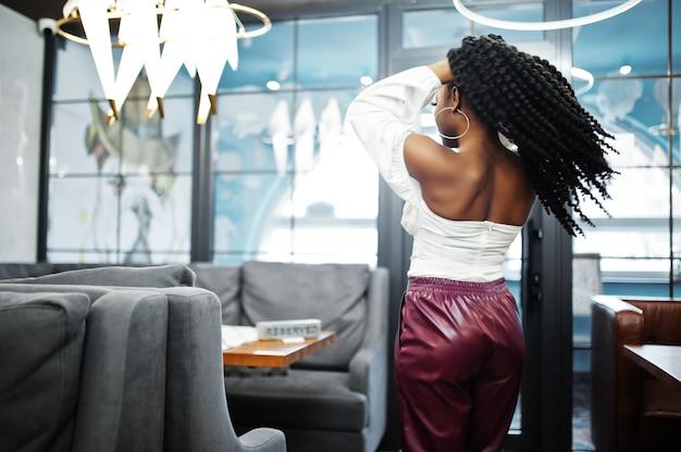 Schöne afroamerikanerfrau in der weißen bluse und in der roten lederhose werfen am restaurant auf.