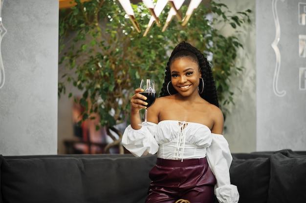 Schöne afroamerikanerfrau in der weißen bluse und in der roten lederhose werfen am restaurant mit glas wein auf.