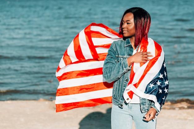 Schöne afroamerikanerfrau mit amerikanischer flagge winken