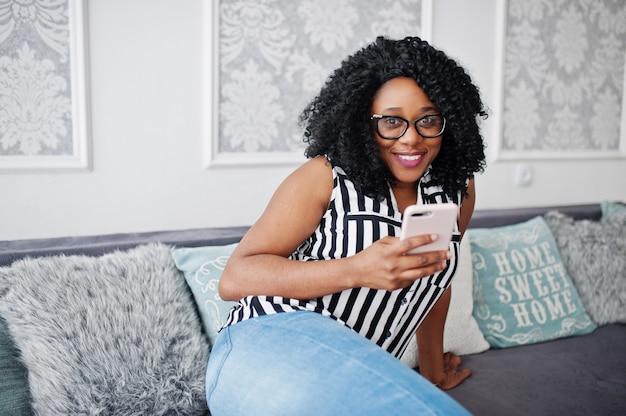 Schöne afroamerikanerfrau mit dem gelockten afrohaar und den brillen, in der hand sitzend auf couch mit handy.
