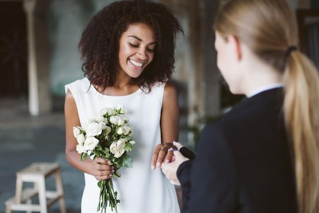 Schöne afroamerikanerfrau mit dunklem lockigem haar im weißen kleid, das kleinen blumenstrauß in der hand hält, während glücklich zeit auf hochzeitszeremonie verbringend