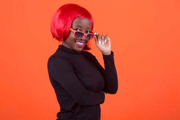 Schöne afroamerikanerfrau mit einer roten perücke