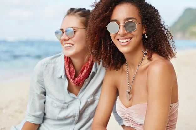 Schöne afroamerikanerin mit dunkler haut und lockigem haar, hat ein positives lächeln, trägt eine sonnenbrille, sitzt in der nähe ihrer freundin, die seelandschaft genießt, genießt eine ruhige atmosphäre am strand. freundschaftskonzept