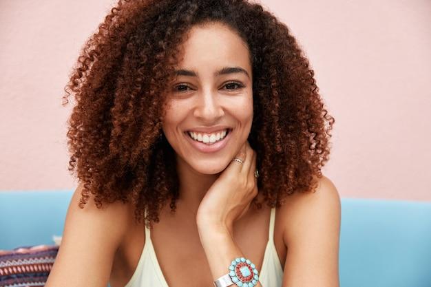 Schöne afroamerikanerin mit lockigem haar, hat weiße perfekte zähne, zieht sich innen vor rosa hintergrund zurück