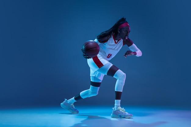 Schöne afroamerikanische basketballspielerin in bewegung und aktion in neonlicht auf blauem wandkonzept des professionellen sporthobby des gesunden lebensstils