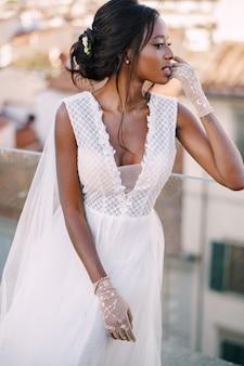 Schöne afroamerikanische braut in einem weißen hochzeitskleid, berührt ihr gesicht in vintage-handschuhen