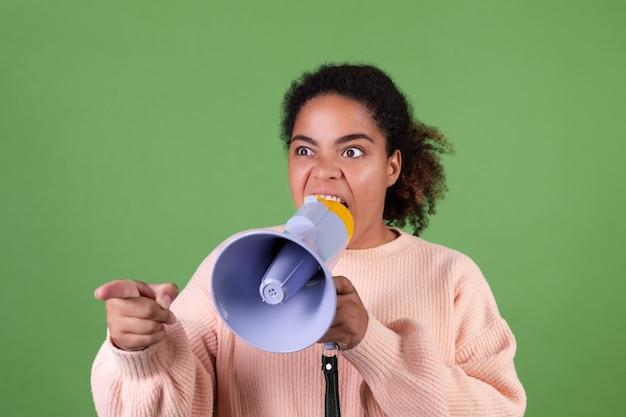 Schöne afroamerikanische frau auf grüner wand, die im megaphon schreit, bittet um aufmerksamkeit