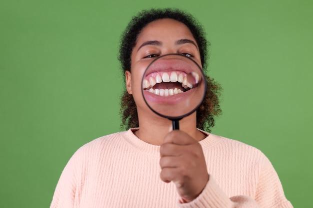 Schöne afroamerikanische frau auf grüner wand mit lupe, die weiße perfekte zähne zeigt