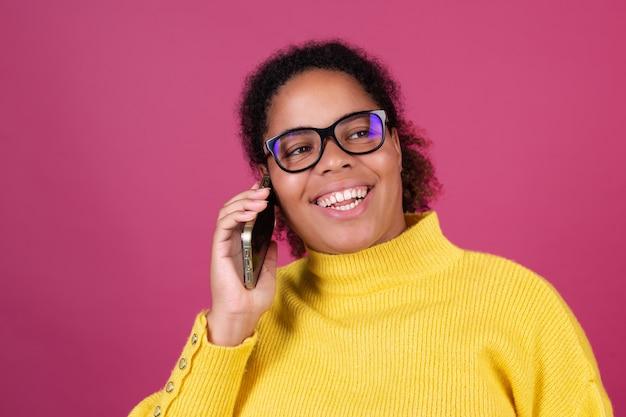 Schöne afroamerikanische frau auf rosa wand, die sich auf dem handy unterhält