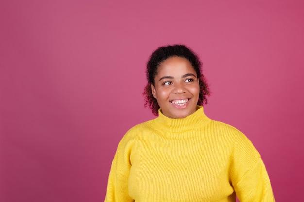 Schöne afroamerikanische frau auf rosa wand glücklich lächelnd fröhlich positiv