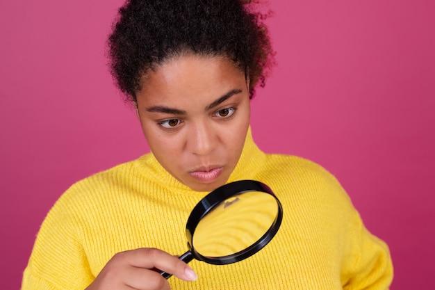 Schöne afroamerikanische frau auf rosa wand mit lupe auf der suche nach
