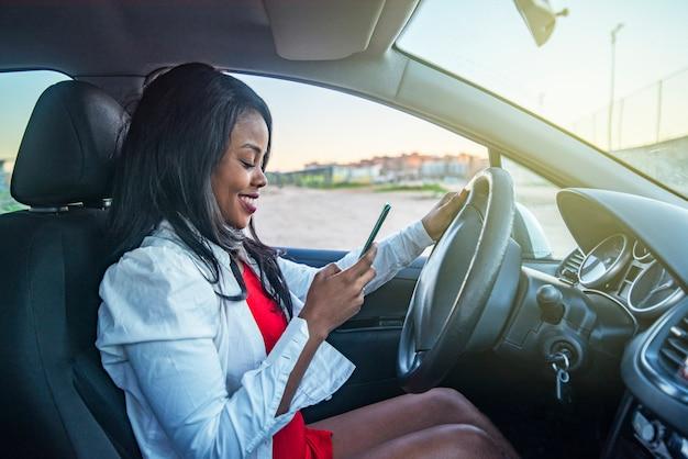 Schöne afroamerikanische frau in einem auto, das ihr handy prüft