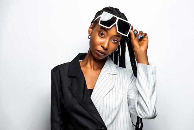 Schöne afroamerikanische frau mit afro-pigtails-frisur und stilvoller kleidung - porträt eines jungen schwarzen mädchens im studio