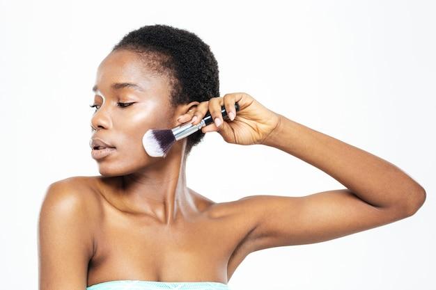 Schöne afroamerikanische frau posiert mit make-up-pinsel isoliert auf weißem hintergrund white