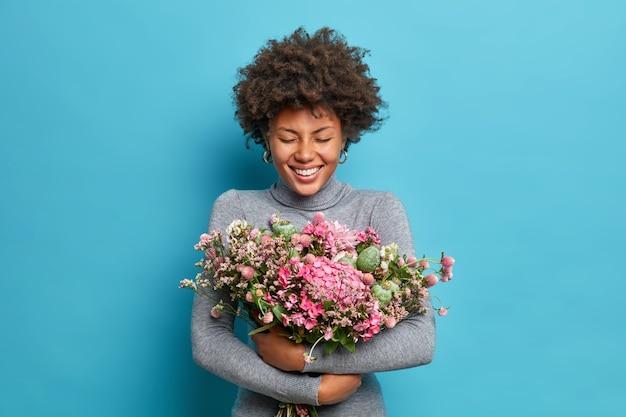 Schöne afroamerikanische frau umarmt blumenstrauß bekommt frühlingsblumen