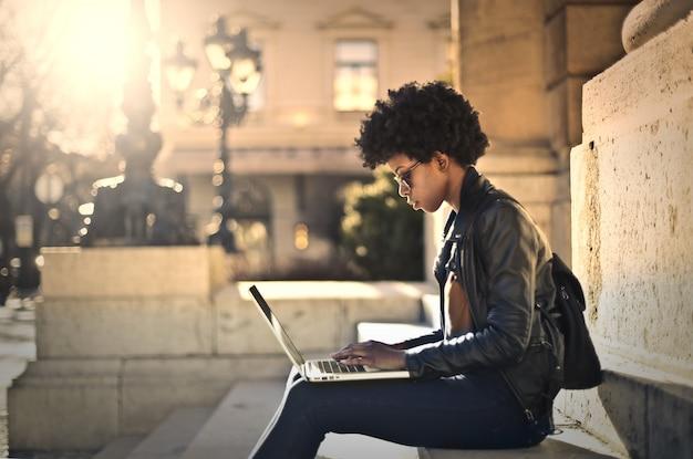 Schöne afrofrau, die an einem laptop arbeitet