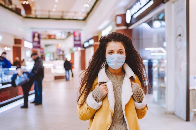Schöne afrohaarige frau, die die schützende medizinische gesichtsmaske im einkaufszentrum trägt.