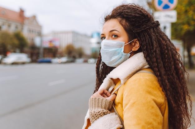 Schöne afrohaarige frau, die die schützende medizinische gesichtsmaske trägt, steht auf der straße der stadt. frau, die soziale distanzierung praktiziert, quarantäne.