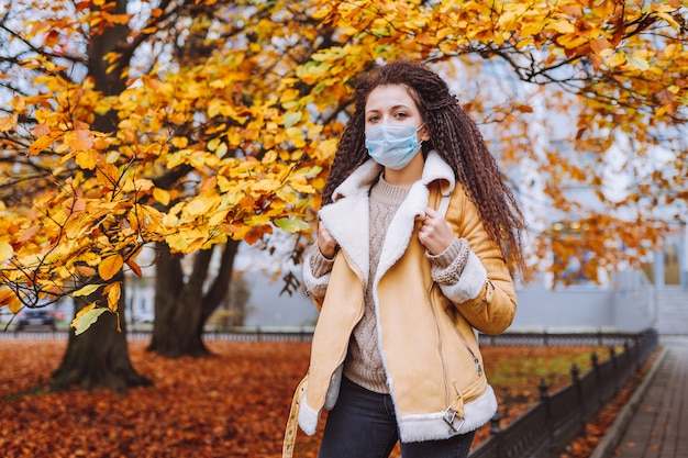 Schöne afrohaarige frau, die die schützende medizinische gesichtsmaske trägt, steht auf der straße der stadt.