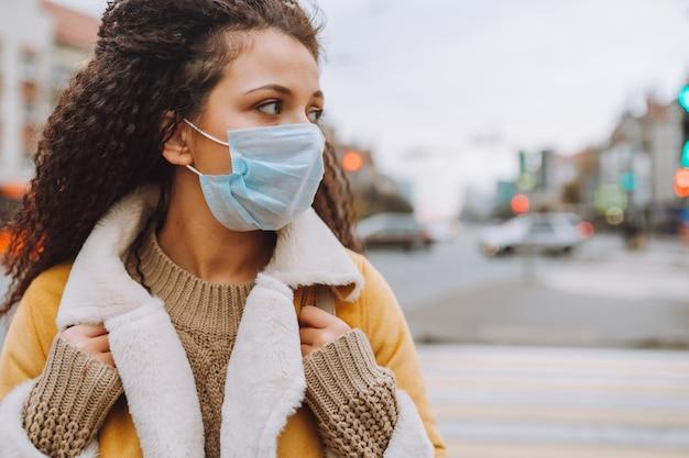 Schöne afrohaarige frau, die medizinische schutzmaske trägt, steht auf der straße der stadt.