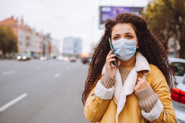 Schöne afrohaarige frau, die schützende medizinische gesichtsmaske trägt, steht auf der straße und spricht per telefon.