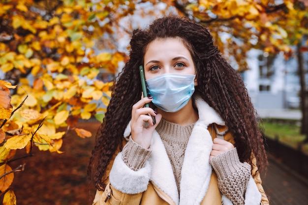 Schöne afrohaarige frau, die schützende medizinische gesichtsmaske trägt, steht auf der straße und spricht per telefon