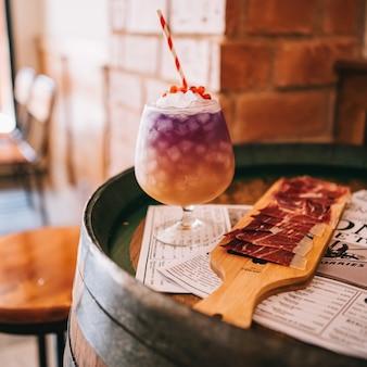 Schöne alkoholische cocktails auf einem holzfass mit einem spanischen schinken