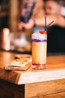 Schöne alkoholische cocktails auf hölzerner bartheke und käsesnack