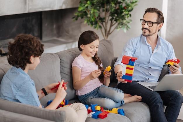 Schöne alleinerziehende, die auf dem sofa sitzt und ein buntes blockset zusammenstellt und scheinbar eine tolle zeit zusammen hat