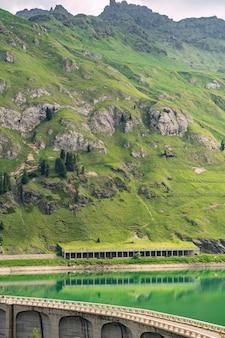 Schöne alpen mit grünem hügel und staudamm am fluss
