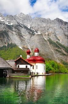 Schöne alpenlandschaft, kristallsee königssee mit kirche