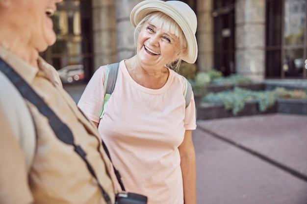 Schöne alte dame mit sonnenhut und ein mann mit einer digitalkamera lacht herzlich