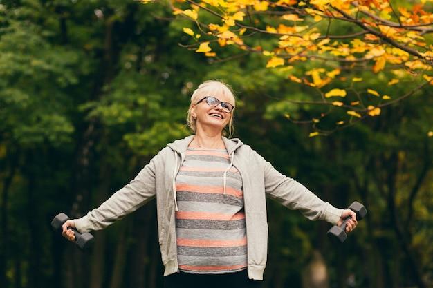 Schöne alte frau, die sich ausruht, lächelnd sport im park macht, übungen mit hanteln macht