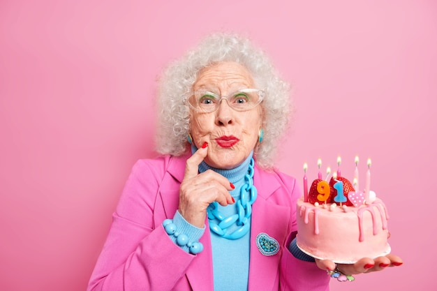 Schöne alte lockige frau trägt make-up roten lippenstift in modischen kostümen gekleidet transparente brille hält kuchen mit brennenden kerzen feiert ihren geburtstag