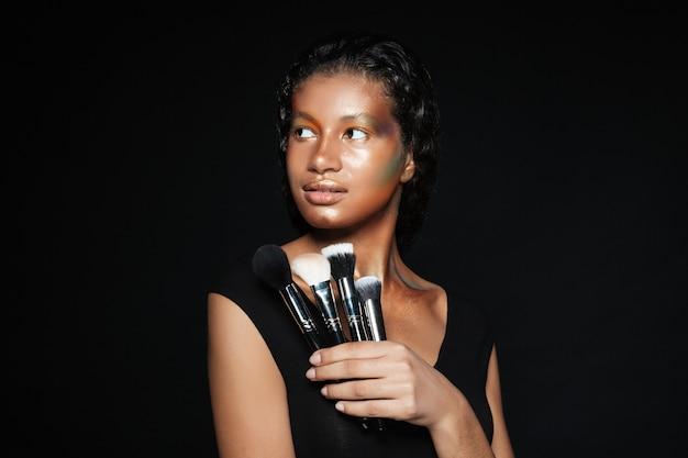 Schöne amerikanische junge frau, die mit make-up-pinseln hält und posiert