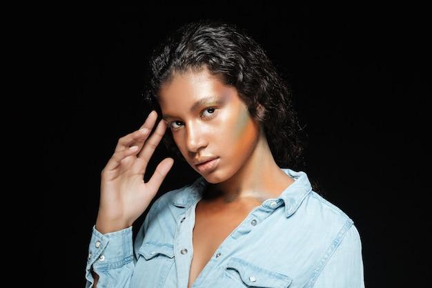 Schöne amerikanische junge frau mit stilvollem make-up, das ihr gesicht über schwarz steht und berührt