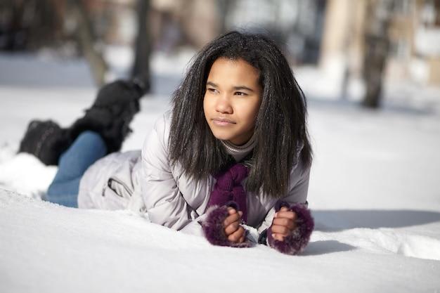 Schöne amerikanische schwarze frau, die draußen im schnee liegt