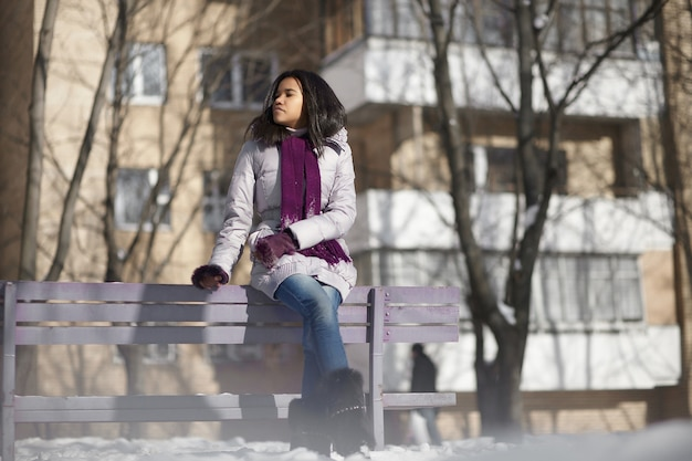 Schöne amerikanische schwarze frau im straßenwinter, der auf einer bank sitzt