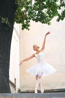 Schöne anmutige ballerina, die auf den straßen eines alten ci tanzt