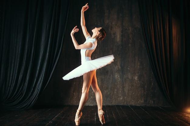 Schöne anmutige ballerina, die im unterricht tanzt. balletttänzerentraining auf der bühne