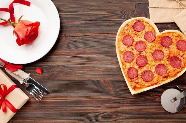 Schöne anordnung für valentinstag abendessen mit herzförmigen pizza